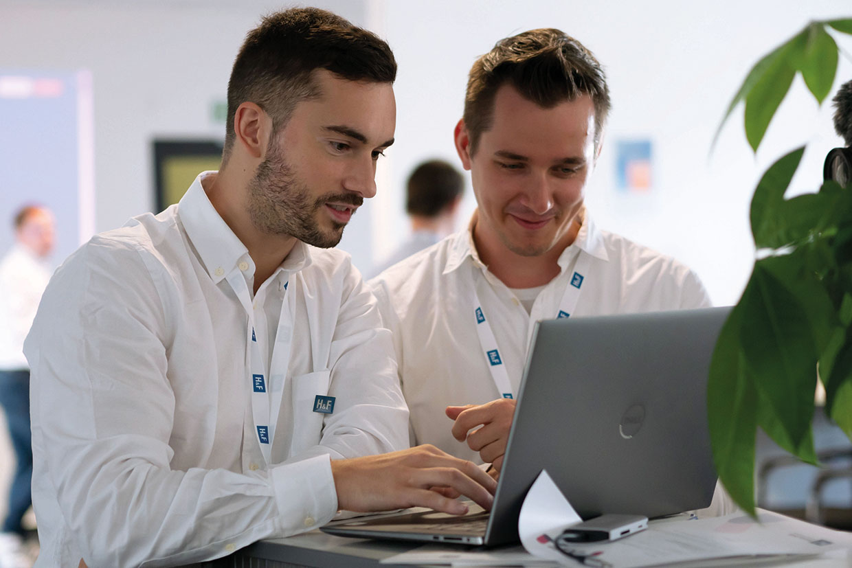 Kollegialer Austausch und Teamgeist im Fokus: Die beiden Software-Entwickler Philipp Schickling und Robin Muskietorz während eines Workshops auf der Entwickler-Konferenz der H&F Solutions.
